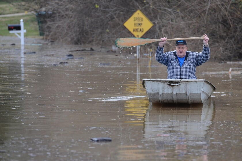 A resident canoes down a street flooded by the Meremac River in Arnold, Mo.