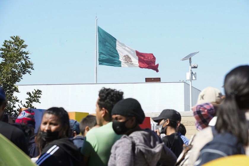 Asylum seekers stand in El Chaparral plaza below the Mexican flag