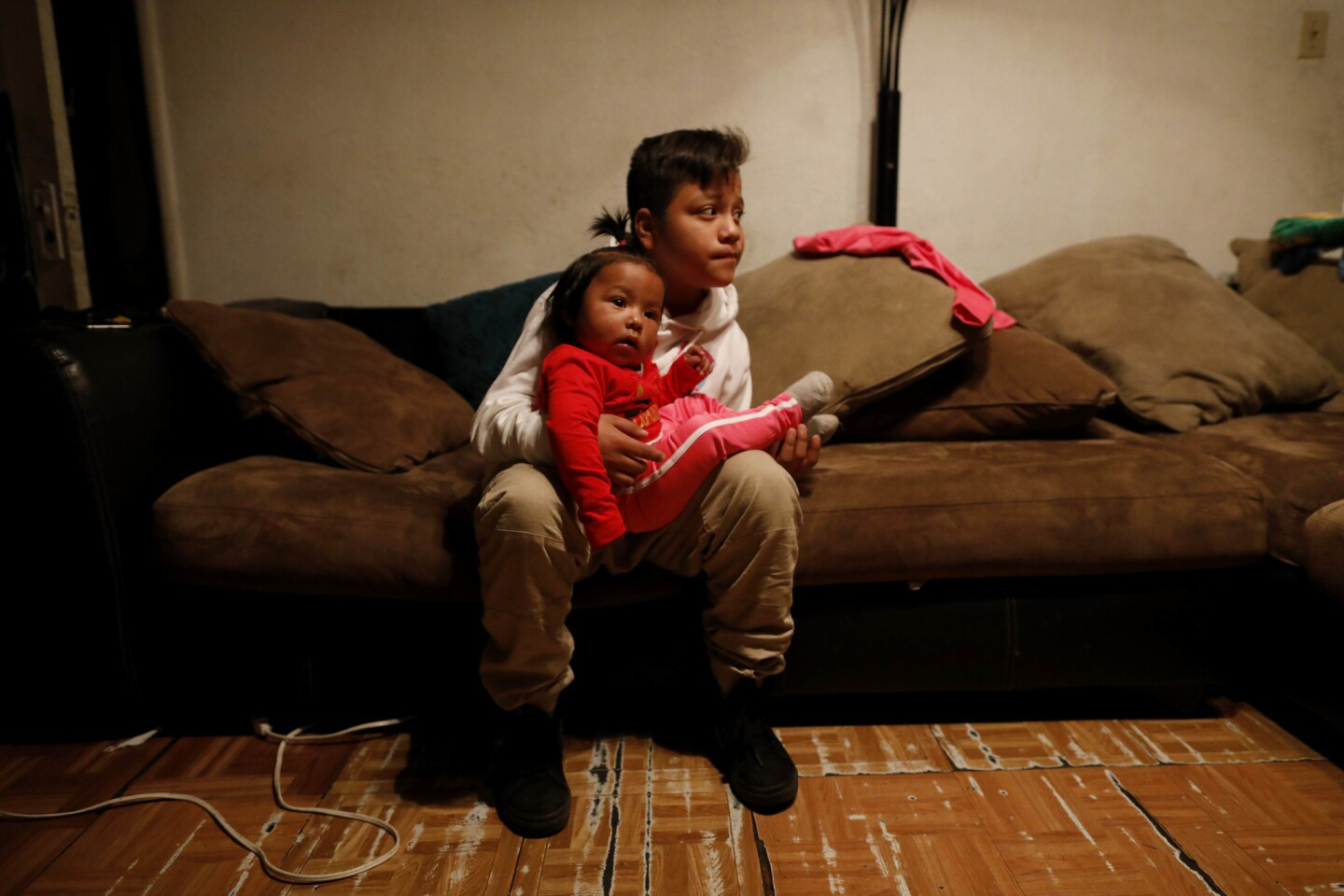 Angel Flores, 11, a fifth-grader at Trinity Elementary School, watches sister Kendy, 12 months, before heading to the picket line at his school. His mother, Kimberly Martinez, decided to keep her children out of school to support the strike.