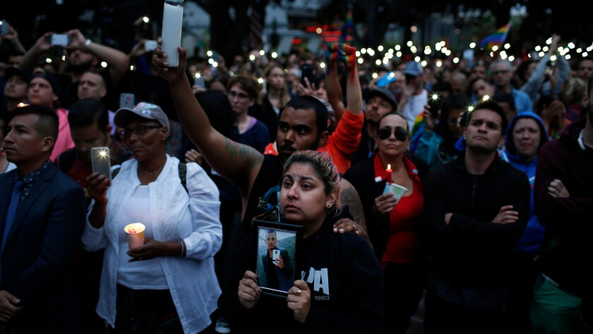 Alison Cossio, center, holds a photo of her friend, Christopher Sanfeliz, who was one of the victims of the Orlando shooting, during a candlelight vigil and rally at Los Angeles City Hall for the victims of Sunday's shooting massacre.