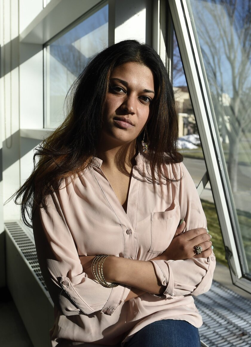 In this Feb. 2, 2016 photo, Naila Amin, 26, sits beside a classroom window at Nassau Community College where she is a student in Garden City, N.Y. Amin, who was forced into marriage at the age of 15 to a 28-year-old cousin in Pakistan who beat and mistreated her, aspires to become a social worker a