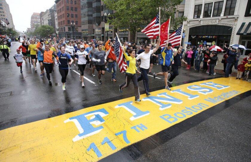 Boston runners finish last mile of the marathon to cheers, hugs