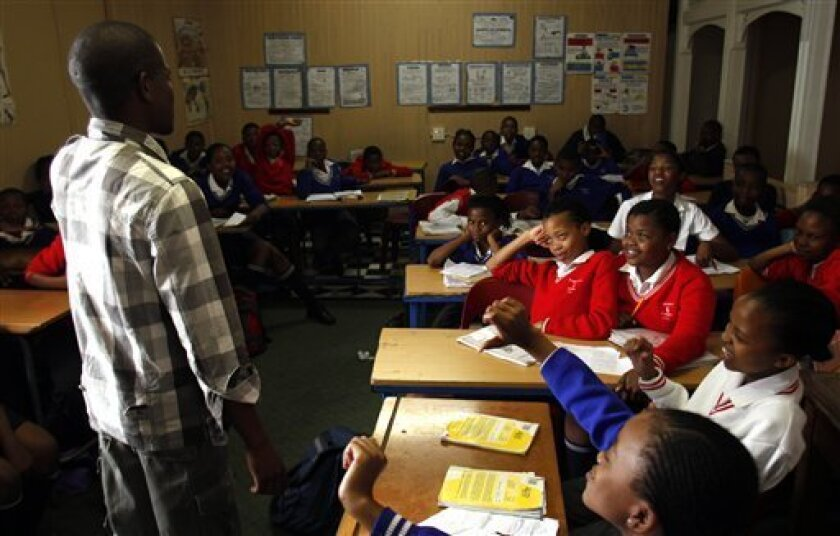 In this Oct. 28, 2010 photo, bible study teacher Micheal Mpubane, left, speaks to pupils in a class at the Progressive Primary in Johannesburg. Progressive Primary is among an increasing number of such schools for poor South Africans underserved by a government that has struggled to close the gap a