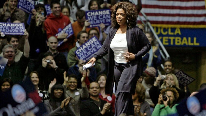 Oprah Winfrey makes her entrance at a campaign rally for then-Democratic presidential hopeful Barack Obama in Los Angeles on Feb. 3, 2008.