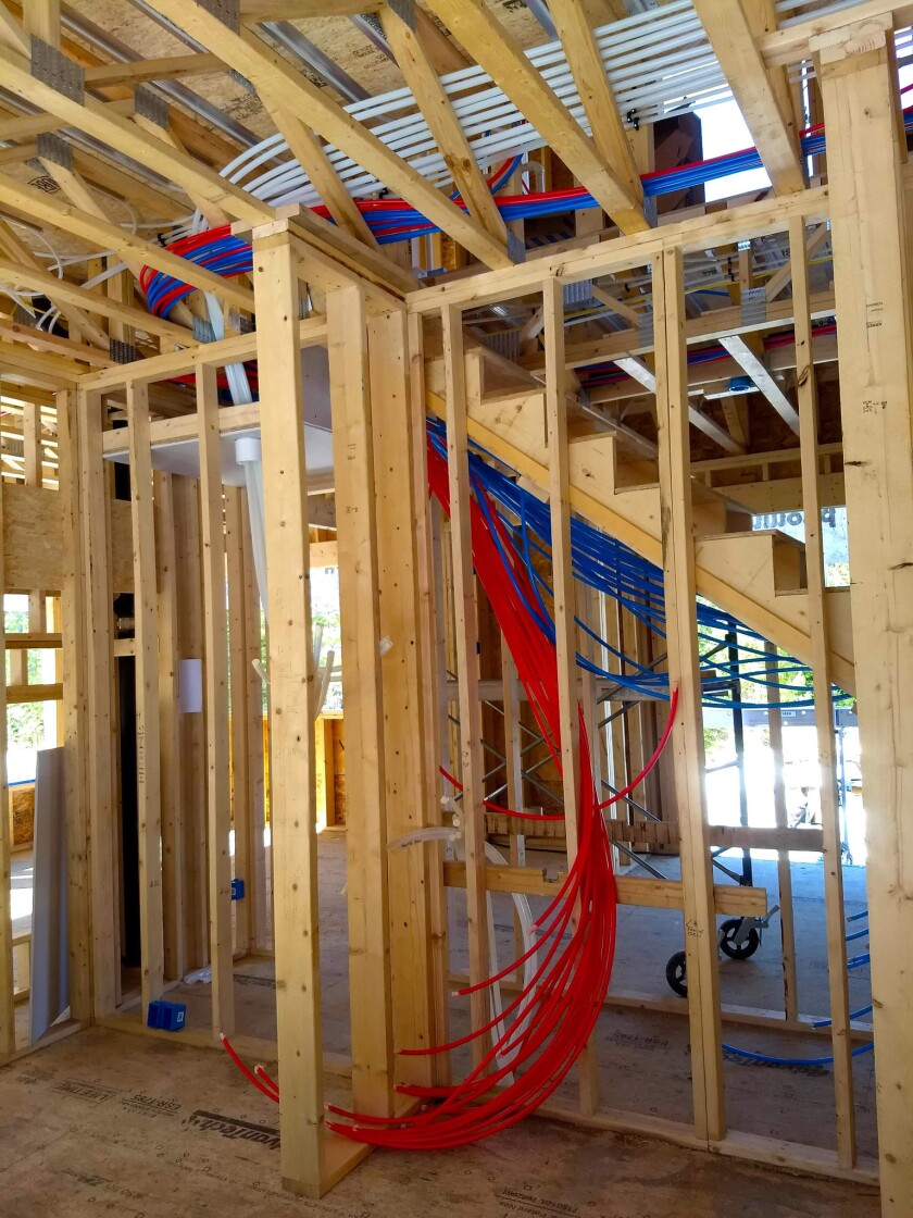 The red and blue PEX pipes will supply hot and cold water to each plumbing fixture in this new home as soon as they're connected to a distribution manifold inside this closet.