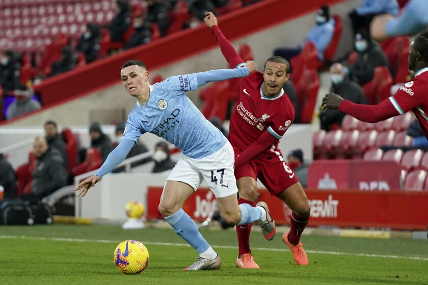 Liverpool's Thiago vies for the ball with Manchester City's Phil Foden, left, during the English Premier League soccer match between Liverpool and Manchester City at Anfield Stadium, Liverpool, England, Sunday, Feb. 7, 2021. (AP photo/Jon Super, Pool)