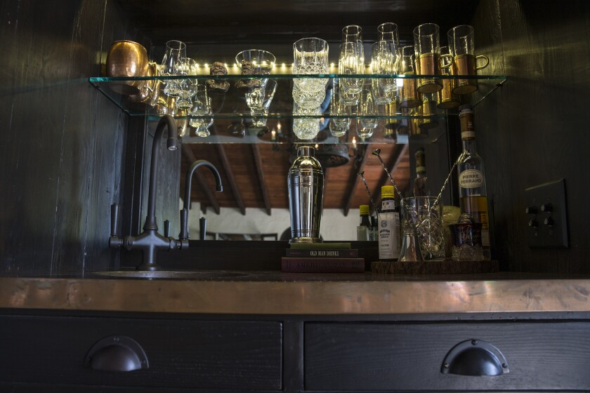 An original beamed ceiling is reflected in a small dining room bar designed by Doherty inside the Mt. Washington home.