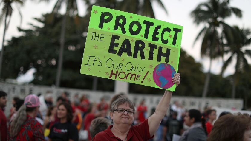 MIAMI, FL - MARCH 08: Judy Byrum holds a sign reading, Protect the Earth, as she joins with others