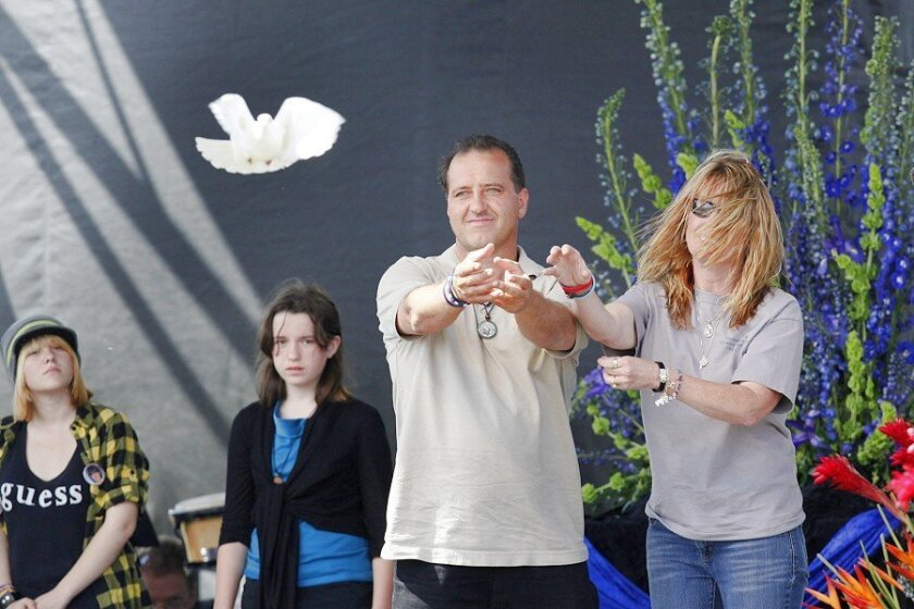 At the end of Saturday's memorial, Amber's parents (above) and three other sets of parents released doves to pay tribute to their slain children.