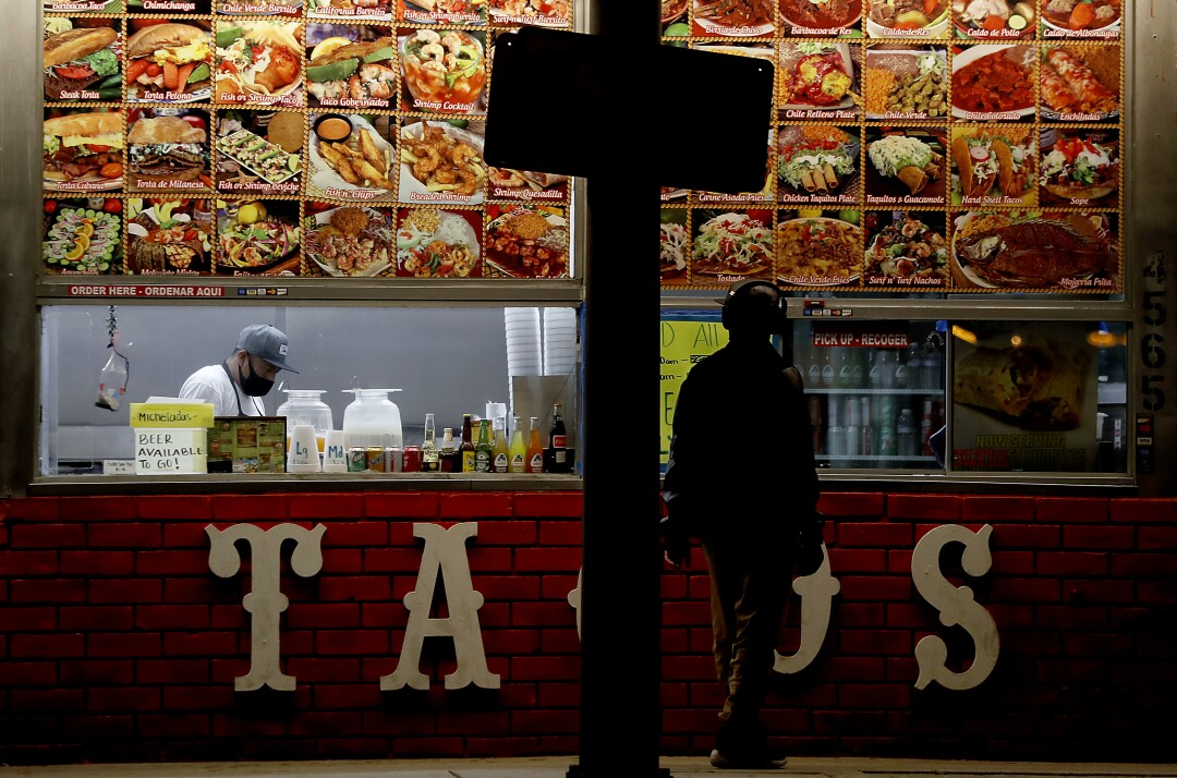 A restaurant worker completes a takeout order for a customer at a taco stand along Redondo Beach Boulevard in Hermosa Beach.
