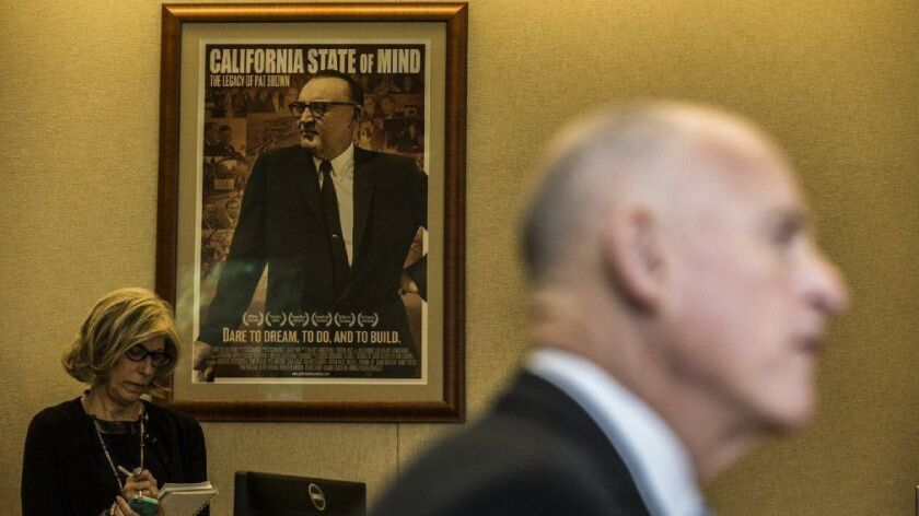 Gov. Jerry Brown gives a news conference near a movie documentary poster picturing his father, former Gov. Pat Brown, in Sacramento in 2014.