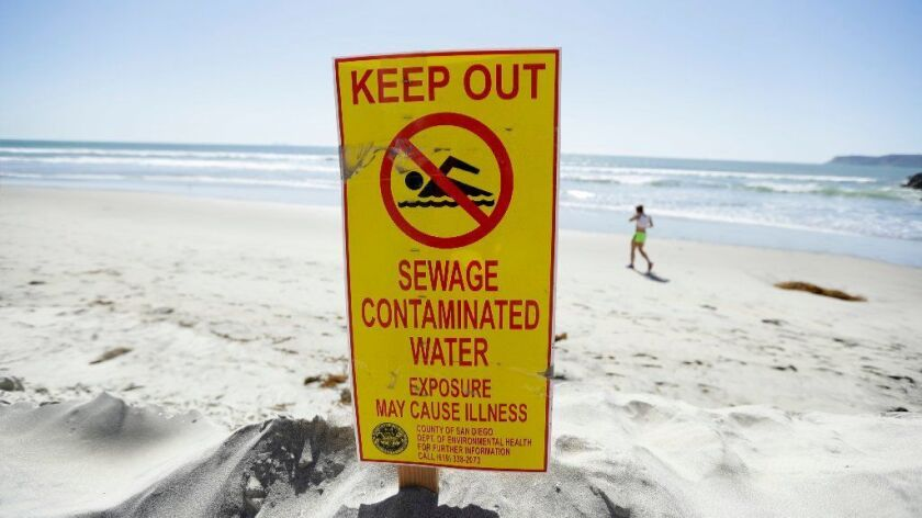 A sign warns of sewage contaminated ocean waters on a beach on March 1, 2017, in Coronado, Calif. Coronado and Imperial Beach waters remain closed to swimmers and surfers after more than 140 million gallons of raw sewage spilled into the Tijuana River, according to a report.