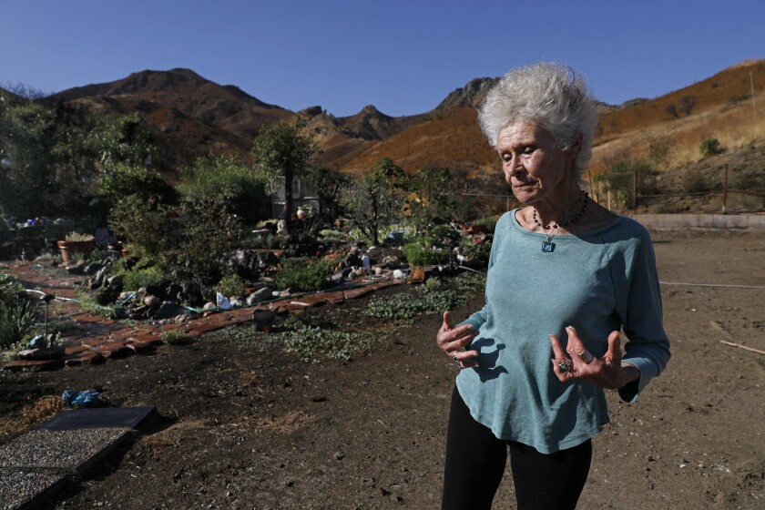 Marsha Maus, 75, stands near the garden at her burned-out lot at Seminole Springs Mobile Home Park in Agoura Hills.