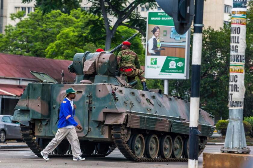 """A man walks past an armored personnel carrier as Zimbabwean soldiers regulate traffic in Harare. Zimbabwe's military appeared to be in control of the country as generals denied staging a coup but used state television to vow to target """"criminals"""" close to President Mugabe."""