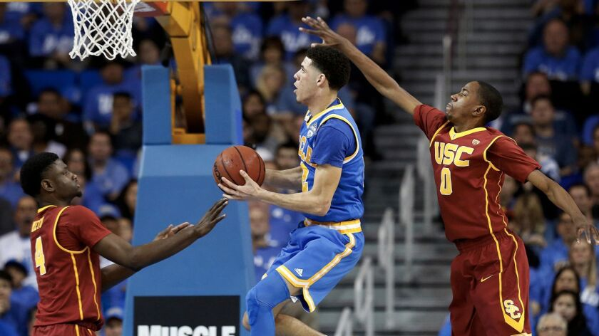 UCLA's Lonzo Ball, center, drives to the basket guarded by USC's Chimezie Metu, left, and Shaqquan Aaron on February 18.