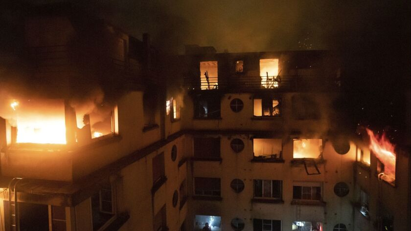 A fire rages through the top floors of an apartment building in Paris on Tuesday.