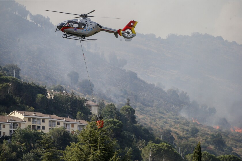 Emergency staff fights a fire on Castillo mountain park near Tivoli a few miles from Rome, Italy, Friday, Aug. 13, 2021. Intense heat baking Italy pushed northward towards the popular tourist destination of Florence Friday while wildfires charred the country's south, and Spain appeared headed for an all-time record high temperature as a heat wave kept southern Europe in a fiery hold. (Cecilia Fabiano/LaPresse via AP)