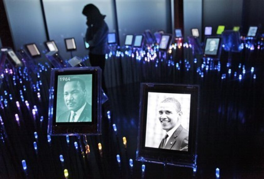 A woman looks at an installation with pictures of 2009 Nobel Peace laureate Barack Obama, right, and 1964 peace laureate Martin Luther King in the Nobel Field at the Nobel Peace Center in Oslo, Norway Tuesday, Dec. 8, 2009. Obama will receive the Nobel Peace Prize on Thursday. (AP Photo/John McConnico)