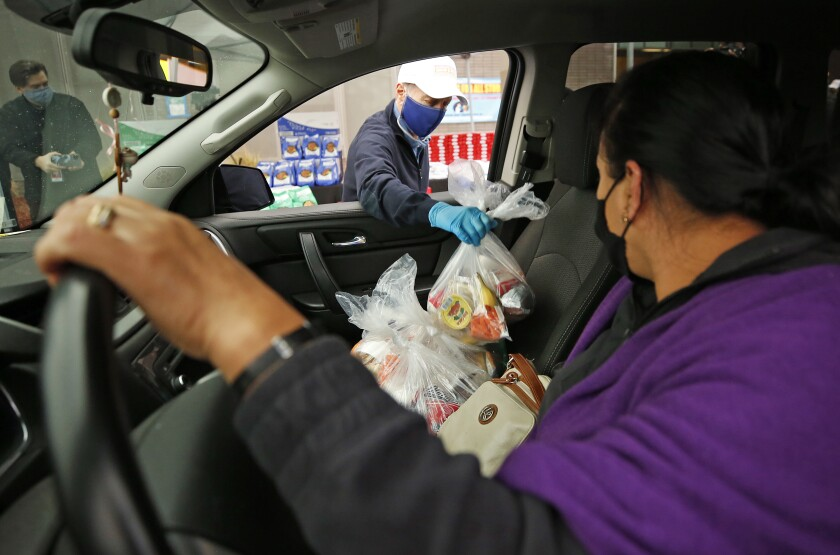 L.A. Unified Supt. Austin Beutner places bags of food in the passenger seat of Manuela Antonio's car.