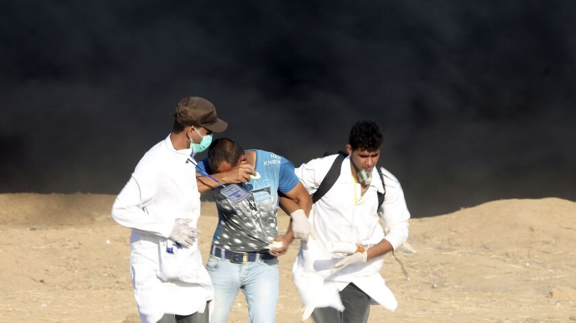 Medics help a protester suffering from teargas fired by Israeli troops near fence of the Gaza Strip