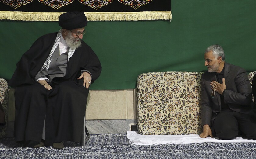 Gen. Qassem Suleimani, kneeling at right, with his hand on his chest, greets Supreme Leader Ayatollah Ali Khamenei, seated in a chair, at a mosque in Tehran.
