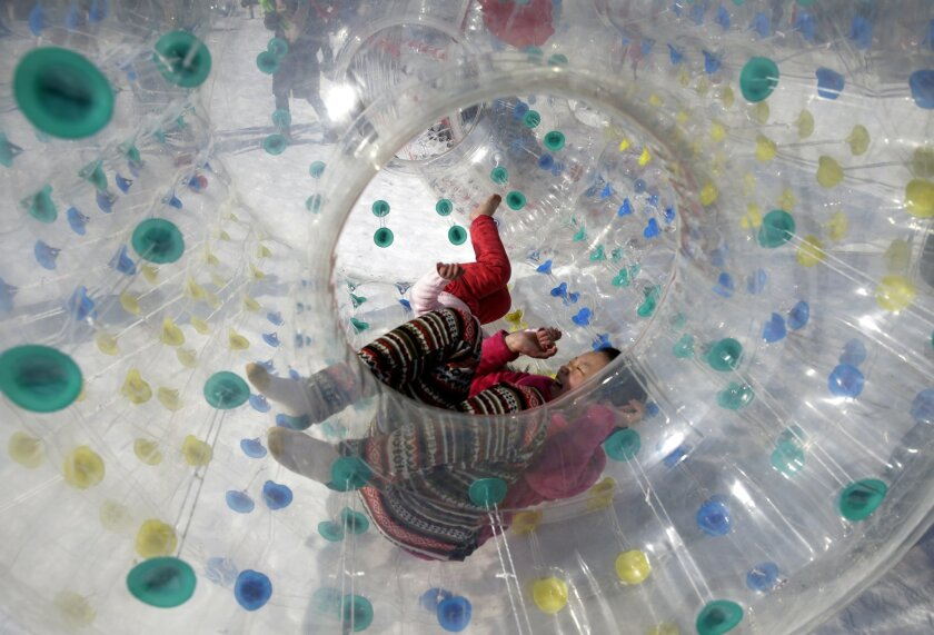 Children play inside an inflatable tube on the snow at Taoranting Park's temple fair for Lunar New Year celebrations in Beijing Monday, Feb. 23, 2015. Chinese people spend a week-long holiday, flocking to public parks' temple fairs to celebrate the Lunar New Year, the Year of the Sheep which started on Feb. 19. (AP Photo/Andy Wong)