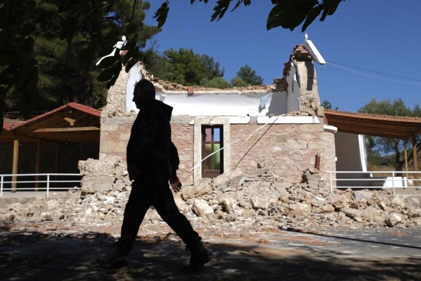 Un vecino pasa junto a una capilla ortodoxa griega dañada por un fuerte sismo