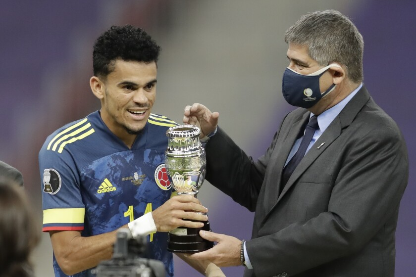 Conmebol General Secretary Jose Astigarraga, right, gives to Colombia's Luis Diaz the best player of the match trophy after beating 3-2 Peru in the Copa America soccer match for the third place at the National stadium in Brasilia, Brazil, Friday, July 9, 2021. (AP Photo/Andre Penner)