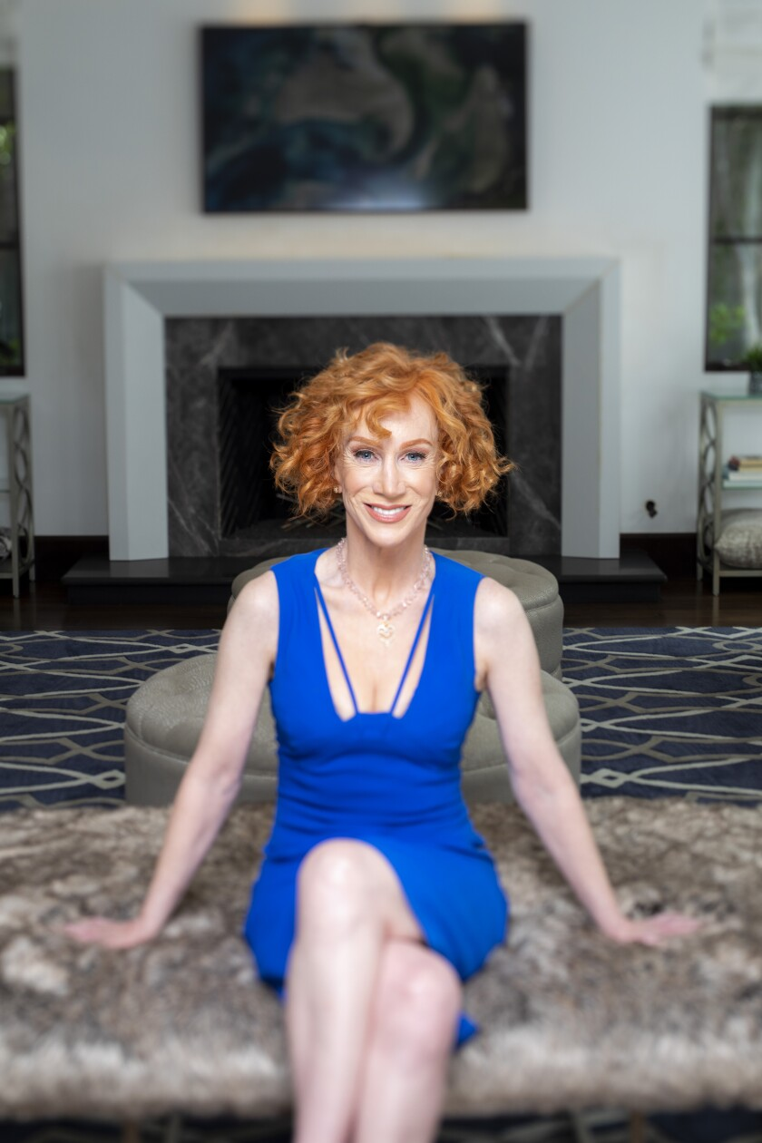 Kathy Griffin seated in her home wearing a blue dress