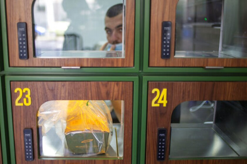 A ready to take away Go Noodles box is placed in a glass-paned locker in Tel Aviv, Israel, Thursday, July 16, 2020. The coronavirus crisis and its economic impact have forced many small businesses and restaurants to shut their doors in recent months, but Tel Aviv's Go Noodles opened a new branch last week that features digital-only ordering and pickup from lockers. (AP Photo/Ariel Schalit)