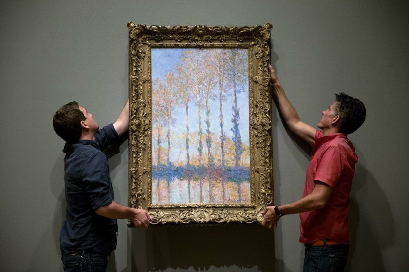 "Staff members Gus Boyce, left, and Eric Griffin place Claude Monet's oil on canvas ""Poplars on the Banks of the Epte River"" ahead of the exhibition ""Discovering the Impressionists: Paul Durand-Ruel and the New Painting,"" Tuesday, June 16, 2015, at the Philadelphia Museum of Art in Philadelphia. The"