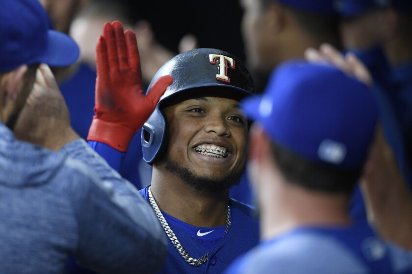 Rangers outfielder Willie Calhoun celebrates in the dugout with teammates after hitting a home run against the Orioles on Sept. 6.