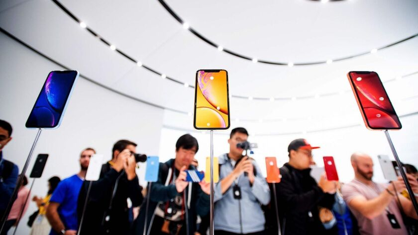 Apple iPhone XR models are displayed during a launch event in Cupertino, Calif. Apple's operating profit last year was $71 billion. Hon Hai, which gets half its sales from Apple for assembling iPhones and other products, earned $4.5 billion.