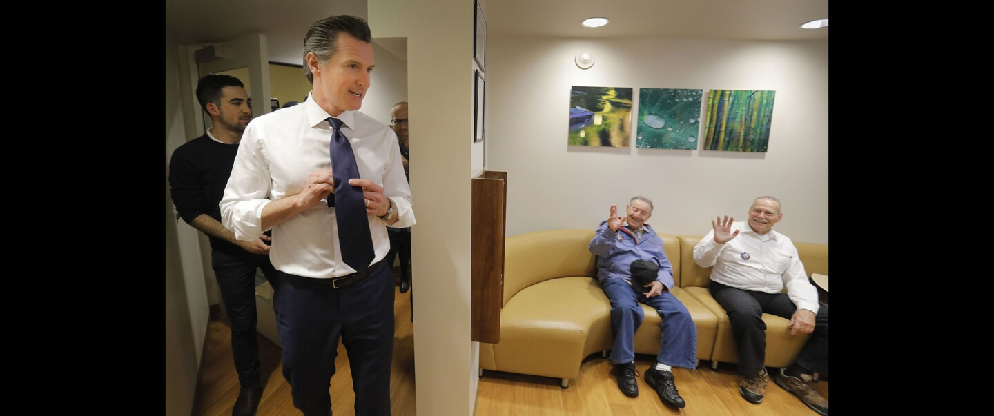 California Lt. Governor Gavin Newsom, a Democrat running for governor, left, is greeted in the dental office at the Gary and Mary West Senior Wellness Center, the Serving Seniors location in downtown San Diego by Rich Gulioni, center, and John Dunlop, right, during a campaign stop.