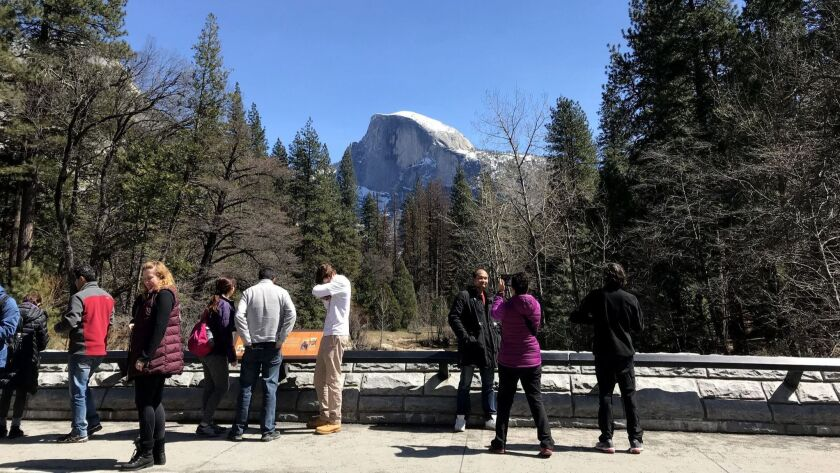 Visitors crowd a bridge to take selfies and photograph the Half Dome in Yosemite National Park in late March.