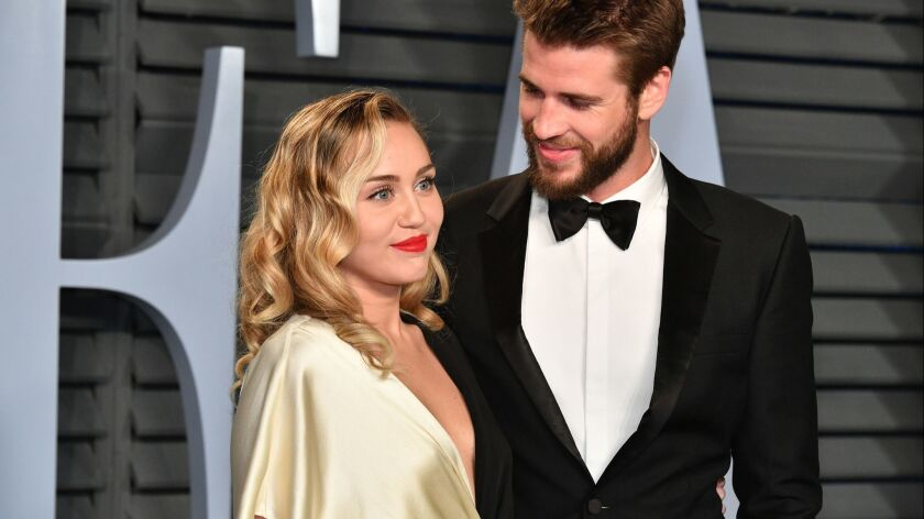 Miley Cyrus, left, and Liam Hemsworth, seen here at the 2018 Vanity Fair Oscar party, have married,