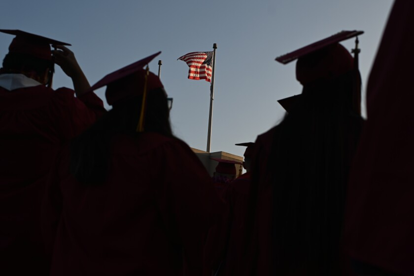 A flag waves between silhouetted graduates