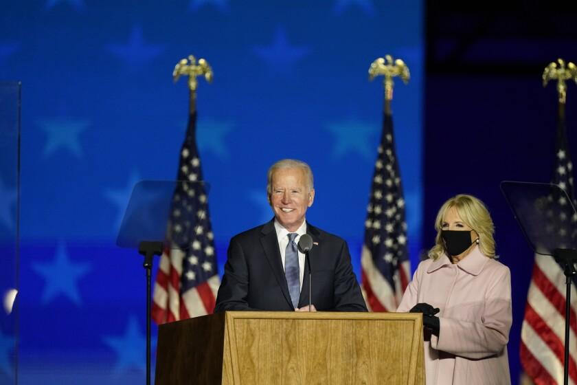Joe Biden speaks at a lectern with wife Jill by his side.