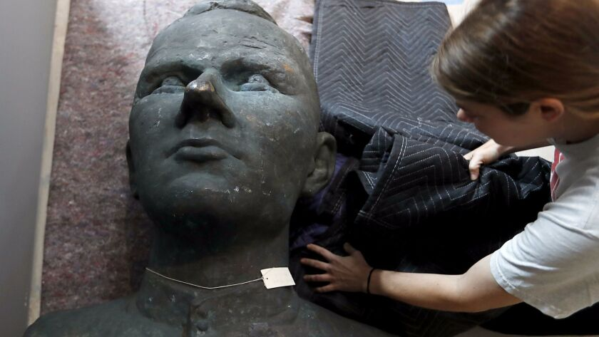 A bust of Russian cosmonaut Yuri Gagarin gets unwrapped for installation.