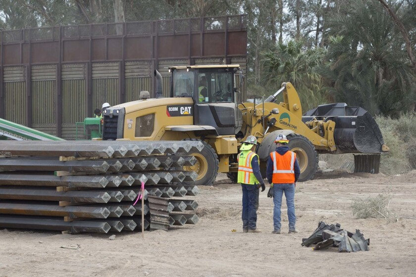 In this 2018 photo from Calexico, prefabricated sections of the new border wall lie stacked atop each other, left, as the foundation for their installation is readied.