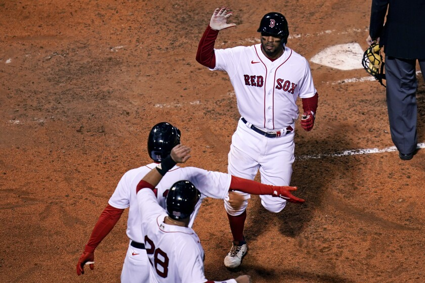 Boston Red Sox's Xander Bogaerts, top, is congratulated by Rafael Devers, center, and J.D. Martinez (28) after scoring on his own double following a throwing error by Tampa Bay Rays catcher Mike Zunino, during the fifth inning of a baseball game at Fenway Park, Monday, April 5, 2021, in Boston. (AP Photo/Charles Krupa)