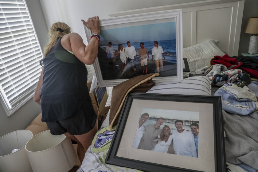 Kym Hilinski searches through boxes of family photos stored in her bedroom as her home is remodeled.