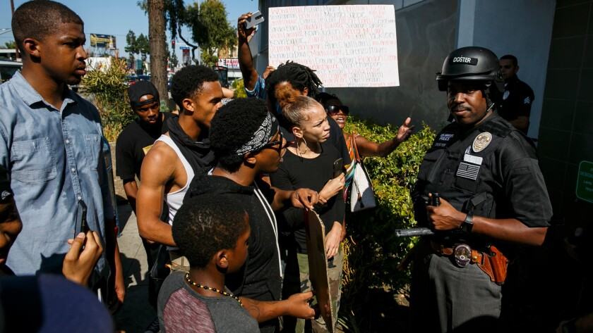 Protesters confront an officer about his race and being a member of the police force at the LAPD's Southwest Community Police Station on West Martin Luther King Jr. Boulevard on July 7.