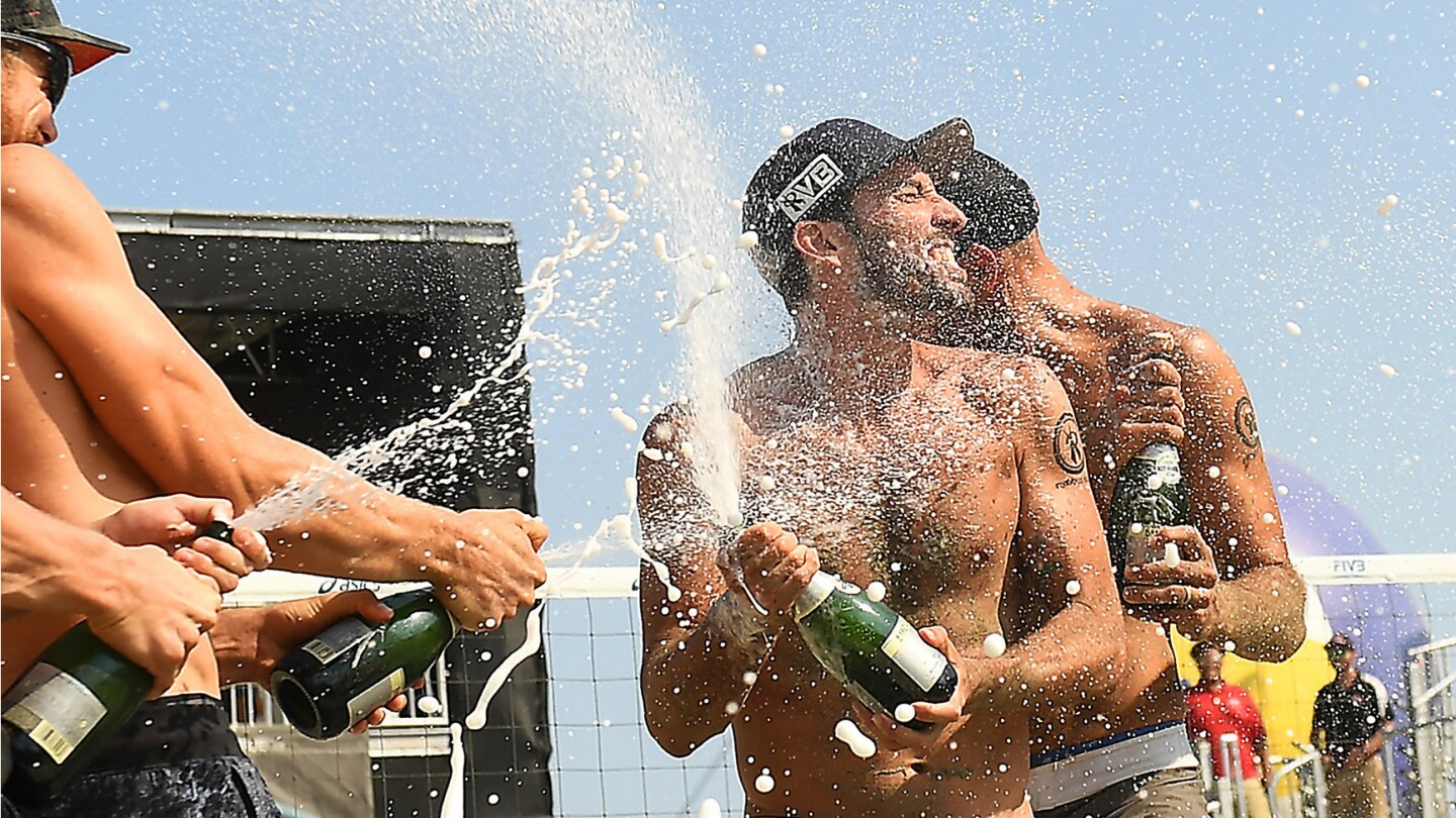 LONG BEACH-CA-JULY 16, 2017: Nick Lucena and Phil Dalhausser, center, are sprayed with champagne after winning 1st place in the World Series of Beach Volleyball in Long Beach on Sunday. (Christina House / For The Times)