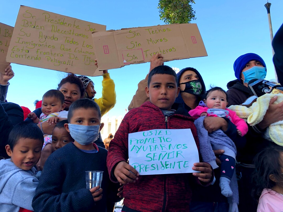 Asylum seekers waiting in Tijuana hold signs asking the United States for help.