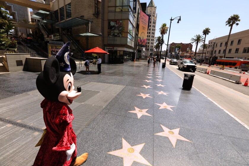 Javie Rubio, dressed as Mickey Mouse, looks for tourists to pose for photos on an empty stretch of Hollywood's Walk of Fame.