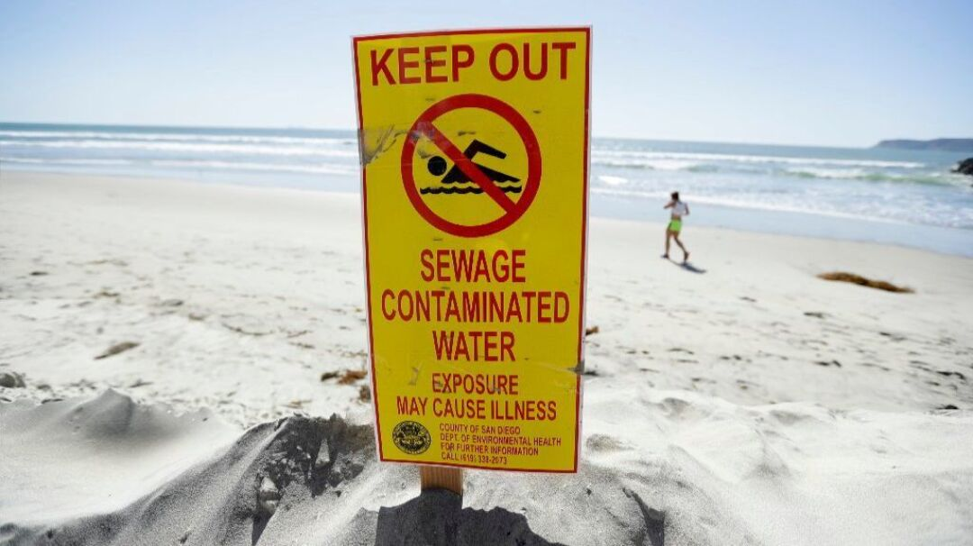 A sign warns of sewage contaminated ocean waters on a beach Wednesday in Coronado after a massive raw sewage spill in the Tijuana River.