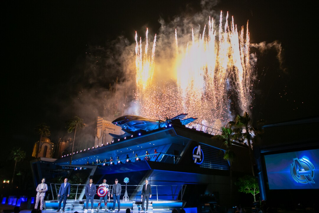 Fireworks go off behind Avengers headquarters as actors and executives stand onstage.