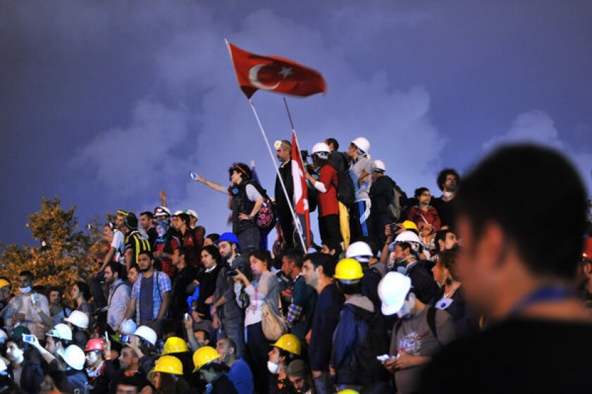 Anti-government protesters unfurl the Turkish national flag in Gezi Park in Istanbul.