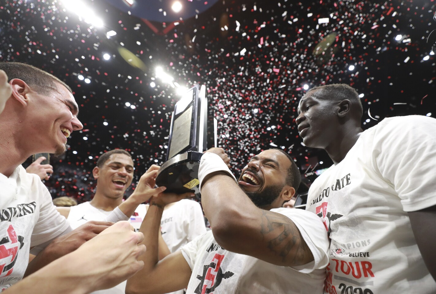 The Aztecs' KJ Feagin holds up the Mountain West trophy as he, Caleb Giordano, left, Matt Mitchell, back left, Aguek Arop, right, and fellow teammates celebrate after the Aztecs defeated New Mexico 82-59 at the Viejas Arena on Tuesday, February 11, 2020 in San Diego, California.